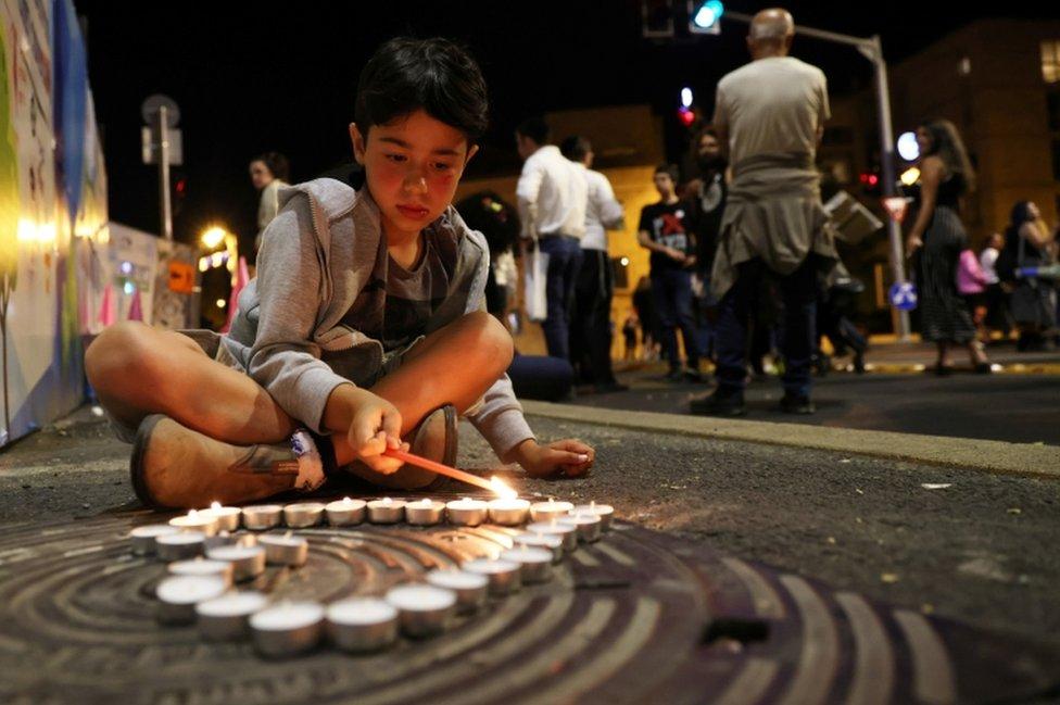 صبي في القدس يوقد شمعة على أرواح الضحايا