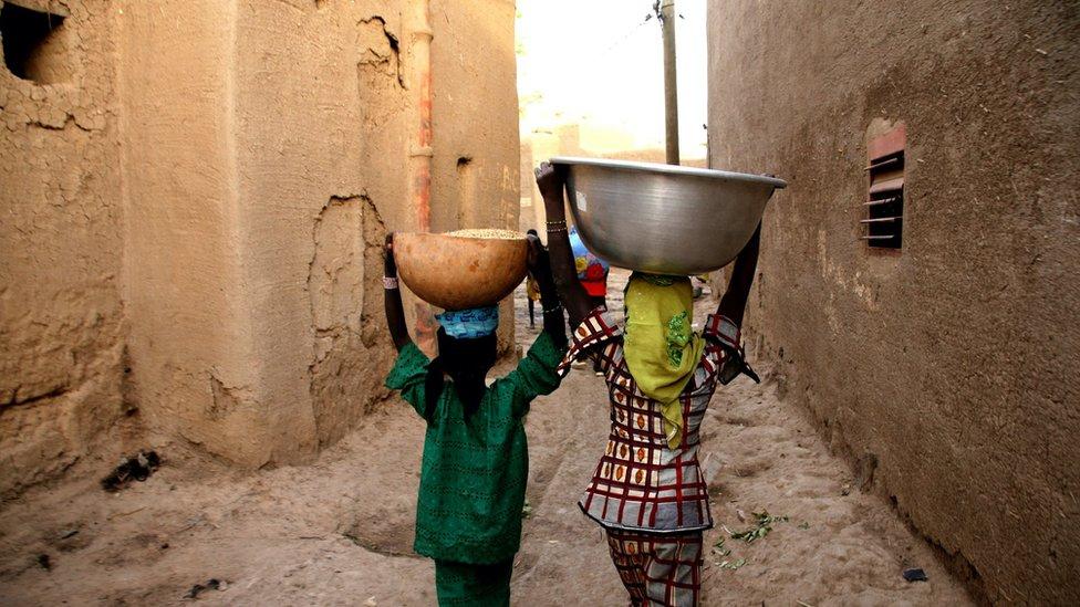 فتاتان تسيران في مدينة ديجينيه في مالي.