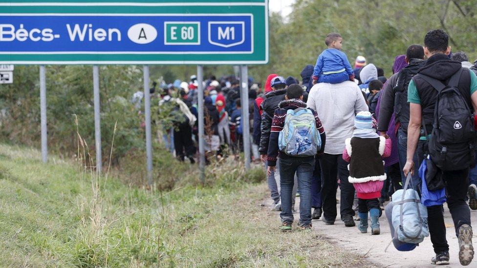 Migrants walk towards the Austrian border in Hegyeshalom,