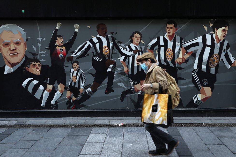 man walks past Newcastle United mural