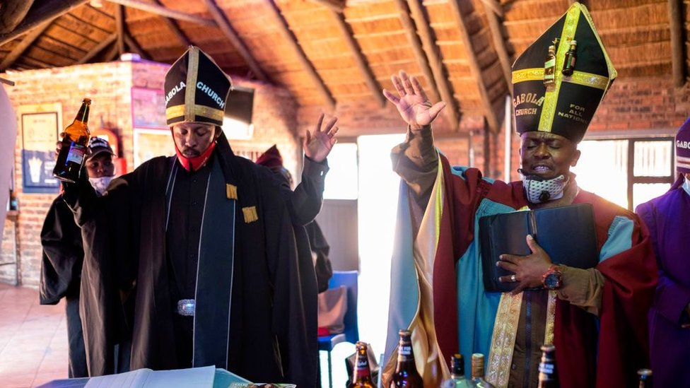 Tsietsi Makiti (R) the founder and leader of Gabola church gestures while praying during the Sunday sermon at Bunny's Tavern in Evaton on August 30, 2020.