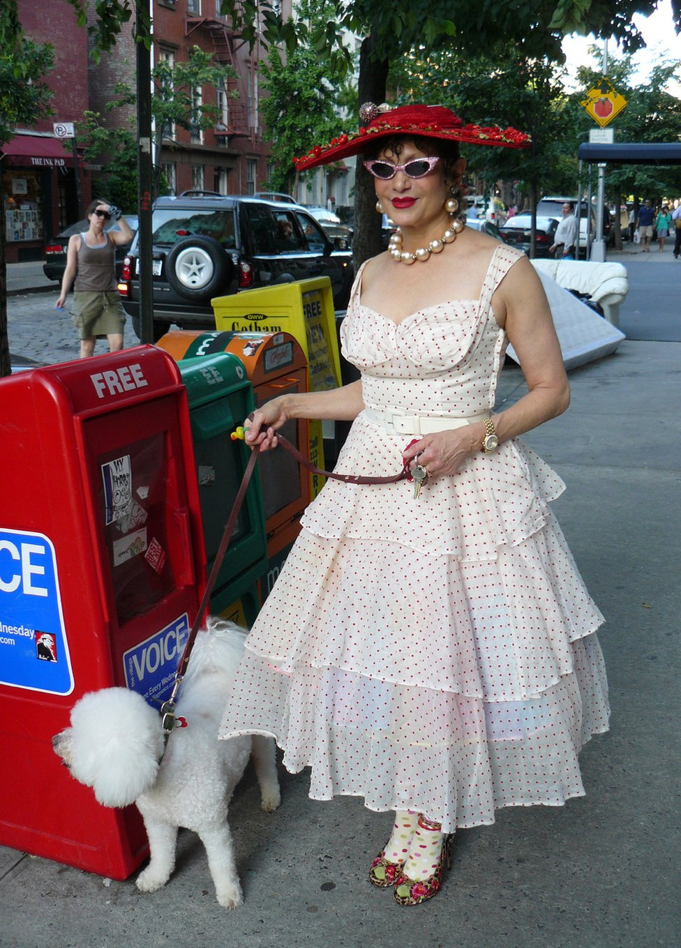 A woman dressed in an 1950s-style polka dot dress walks her dog