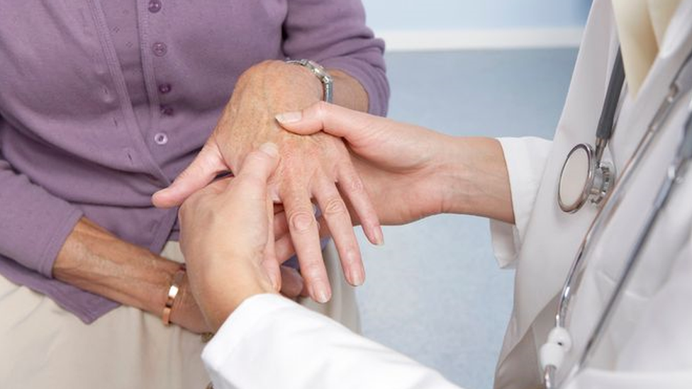 Profissional de saúde de avental branco analisa as articulações da mão de uma mulher