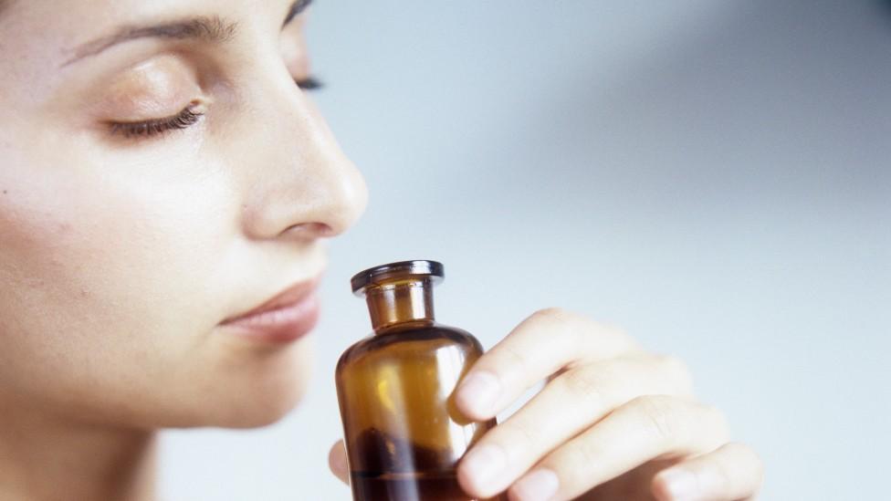 Mujer inhalando de un frasco con los ojos cerrados