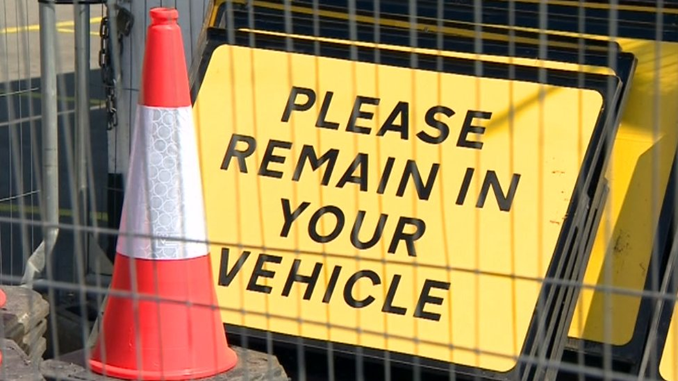 Please remain in your vehicle sign