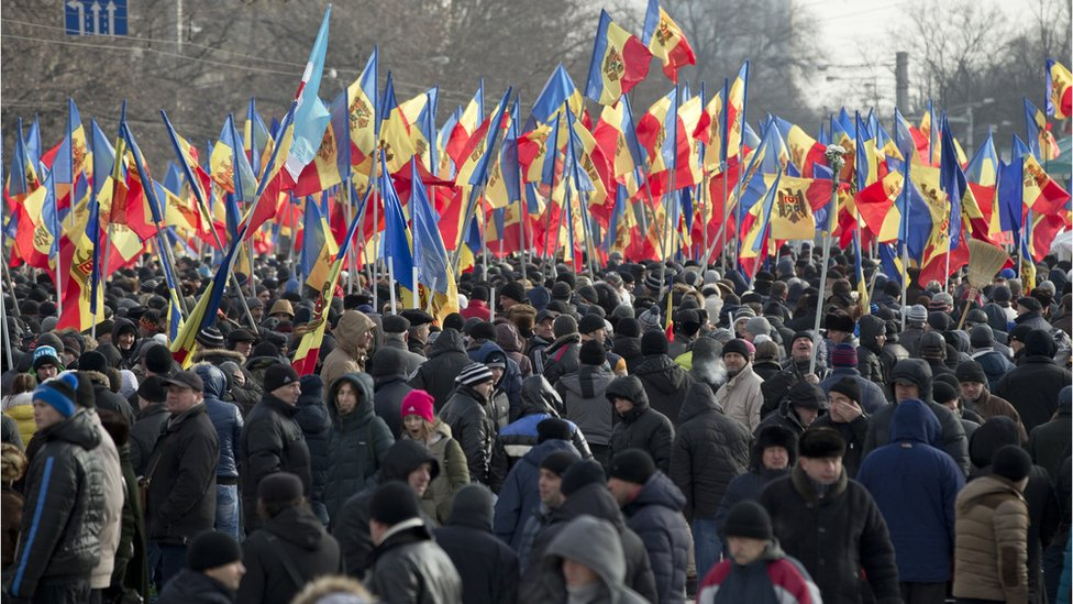 People hold flags during a large protest in Chisinau, Moldova, Sunday, Jan. 24, 2016