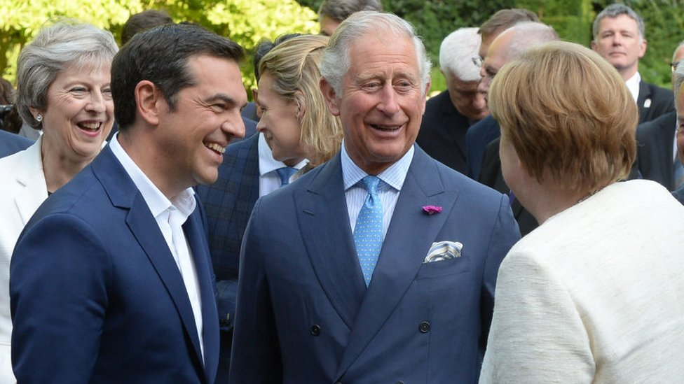 Theresa May (L), Greek Prime Minister Alexis Tsipras (2L) and German Chancellor Angela Merkel speak to Prince Charles (C), in the gardens of St James's Palace in central London following the Western Balkans summit on 10 July 2018