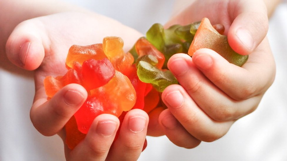 Un niño con caramelos en la mano