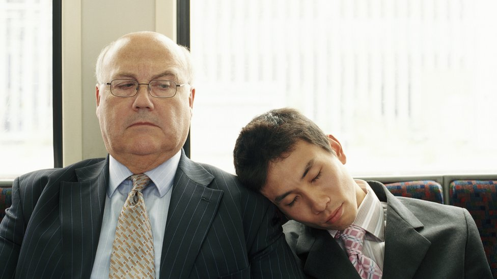 Young man asleep on another man's shoulder