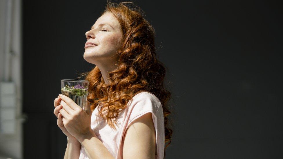 Una mujer respira con un vaso de agua en la mano.