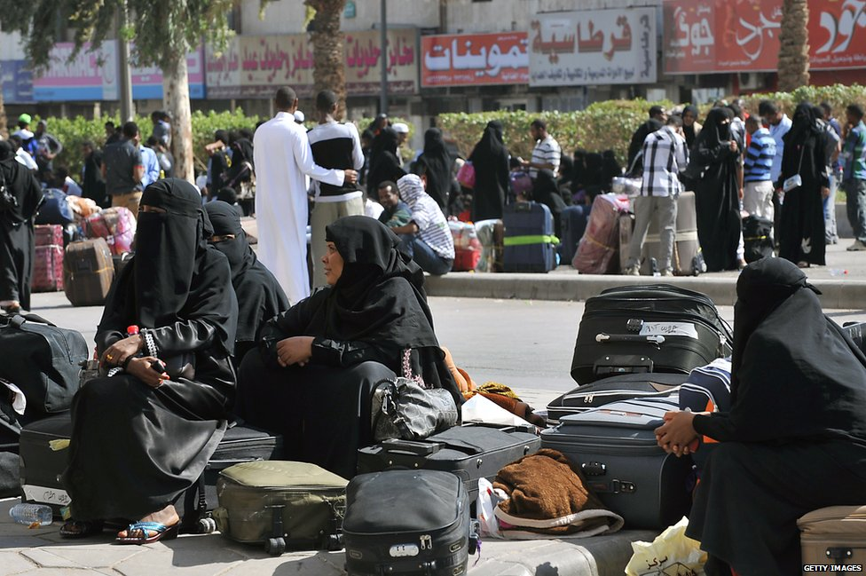 Foreign workers wait with their belongings before boarding police buses in Riyadh