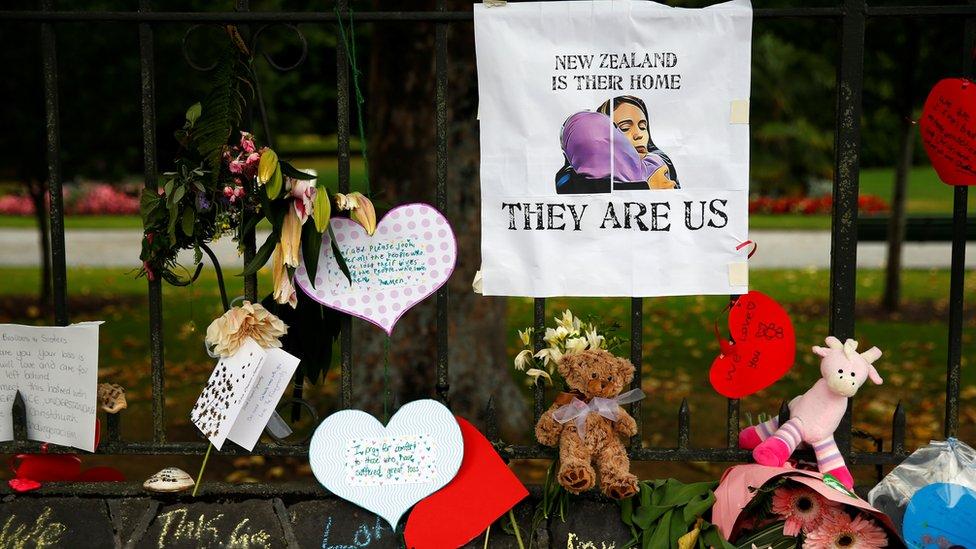 """وسط باقات الزهور، وضعت صورة لرئيسة الوزراء النيوزيلندية جاسيندا أرديرن تعانق سيدة محجبة وتحتها عبارة أطلقتها جاسيندا تقول """"نيوزيلندا وطنهم .. هم نحن""""."""