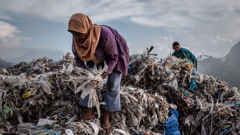 A woman collecting plastic to recycle at a import plastic waste dump in Mojokerto, East Java, Indonesia in December 2018.