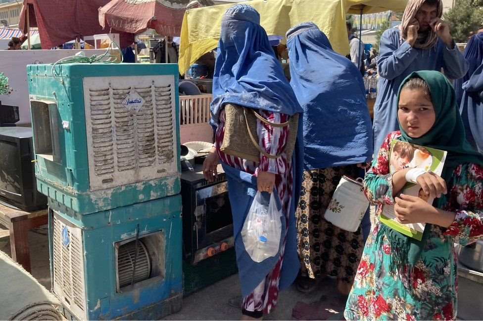 فتاة في سوق للأغراض المستعملة في مزار الشريف في أفغانستان حيث اضطر بعض الأفغان لبيع ممتلكاتهم لتغطية نفقاتهم