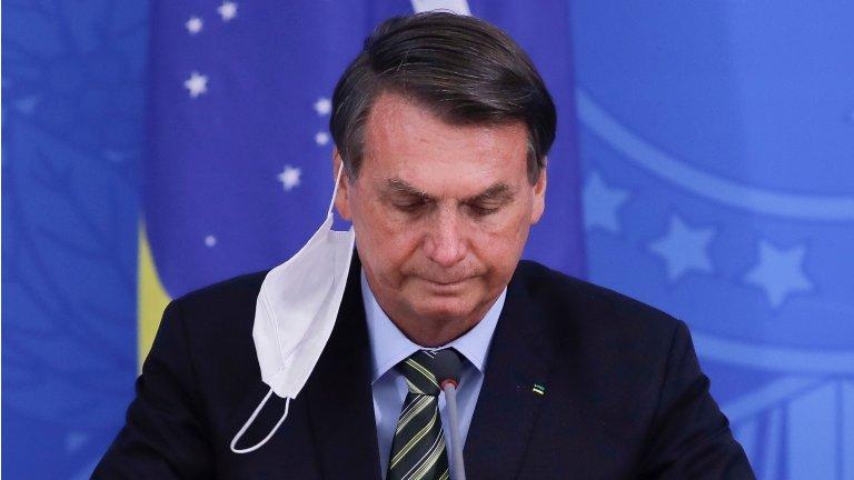 n this file photo taken on March 18, 2020 Brazilian President Jair Bolsonaro gestures during a press conference regarding the COVID-19 coronavirus pandemic at the Planalto Palace, Brasilia