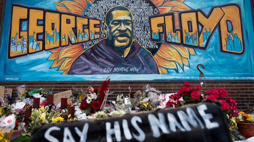أكاليل من الورود موضوعة أسفل جدارية للأمريكي أسود البشرة جورج فلويد الذي قتلته الشرطة، في مينيابوليس، الولايات المتحدة