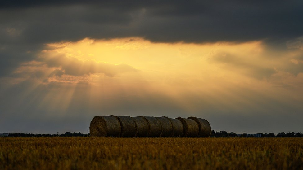 The sun shines through dark clouds onto large straw bales in a field