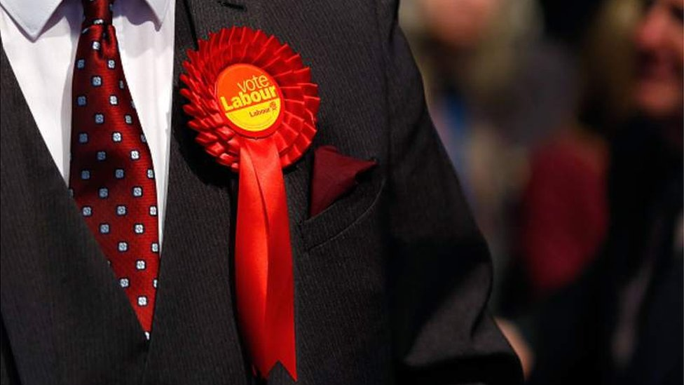Man in suit wearing a Labour rosette