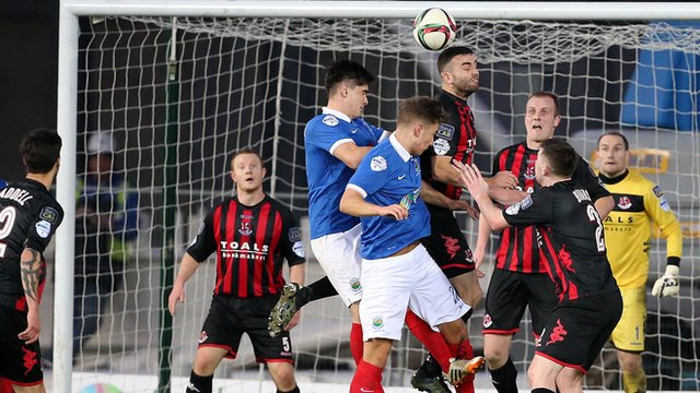 Colin Coates rises highest to head clear as Linfield attack