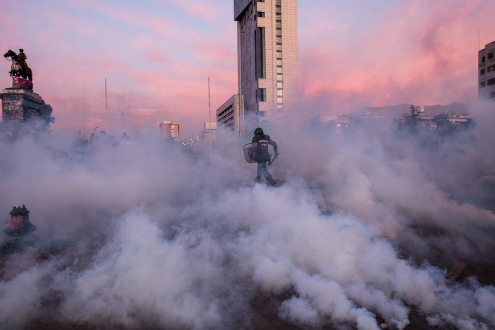 Police officer in riot gear runs amidst smoke bombs towards protesters