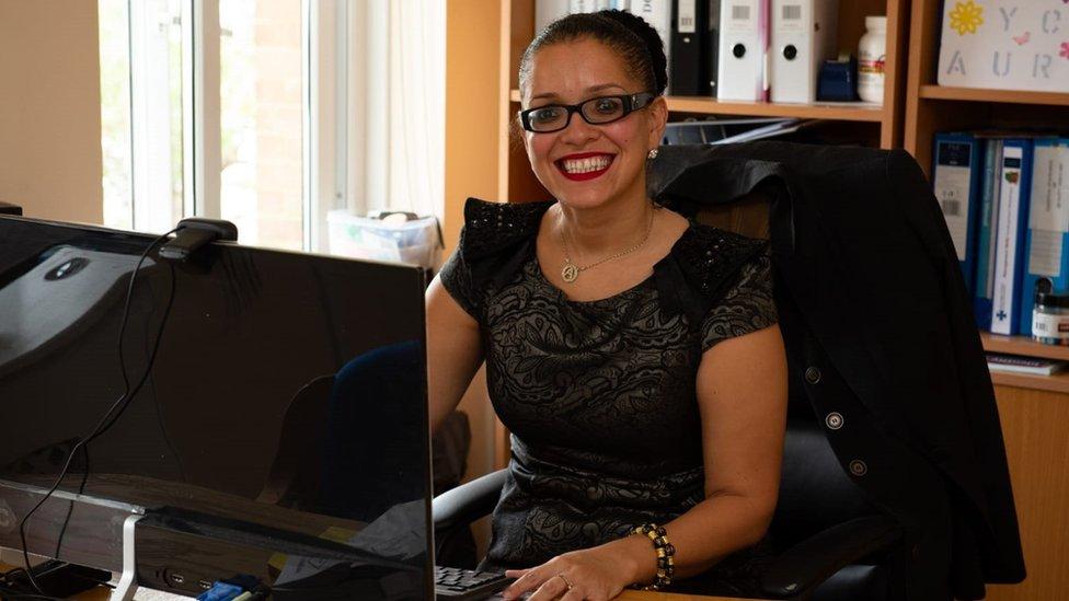 A brasileira Áurea de Souza sorri em sua mesa de trabalho