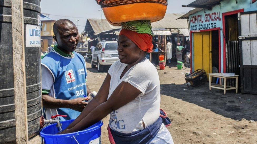 Una mujer se lava las manos con cloro mientras un trabajador de la asiste en una estación de lavado el 15 de julio de 2019 en Goma.
