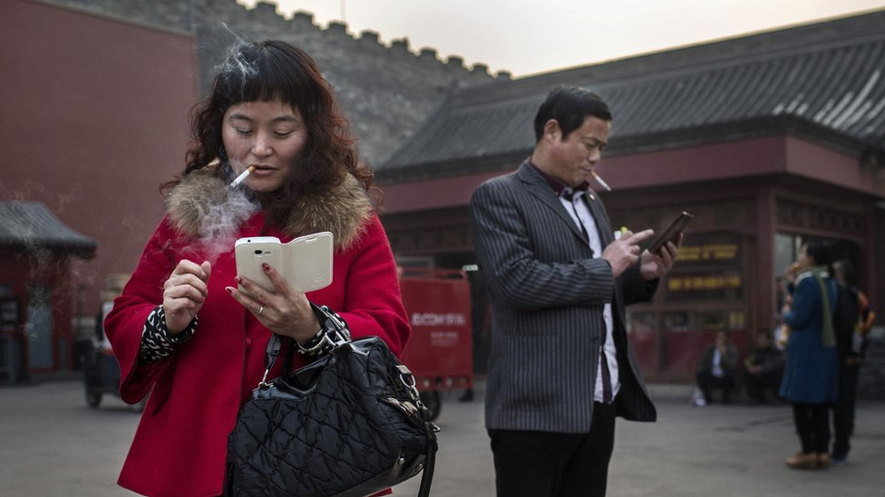 People using mobile phones in China