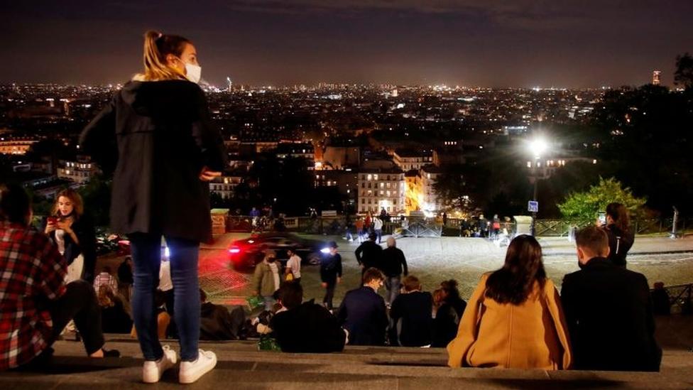 Diversos jovens sentados em escadaria com roupas de frio, à noite, diante de vista da parte baixa de Paris