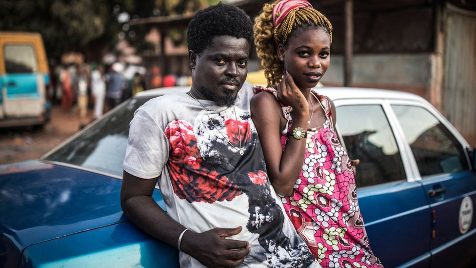 A couple leaning against a car in Bissau, Guinea-Bissau - Sunday 24 November 2019