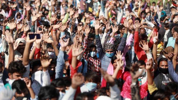 يرفع العمال المهاجرون أيديهم بينما يسألهم رجال الشرطة عن وجهتهم وهم ينتظرون الحافلات على طول الطريق السريع مع عائلاتهم أثناء عودتهم إلى قراهم، خلال فترة إغلاق لمدة 21 يوماً على الصعيد الوطني للحد من انتشار مرض فيروس كورونا، في غازي آباد، على مشارف نيودلهي، الهند، 28 مارس/أذار 2020