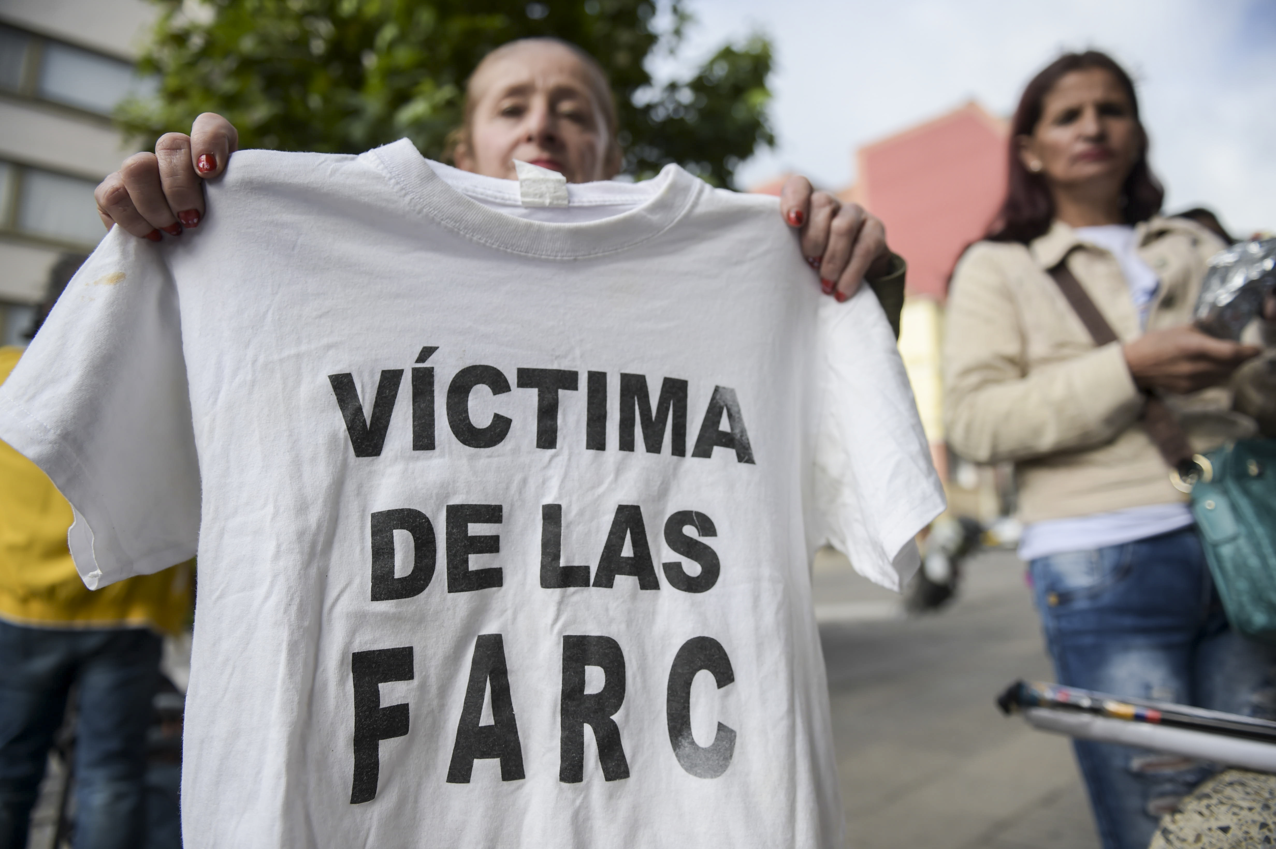 "A woman holds up a T-shirt reading ""Victim of the Farc"" outsider the JEP in Bogota"