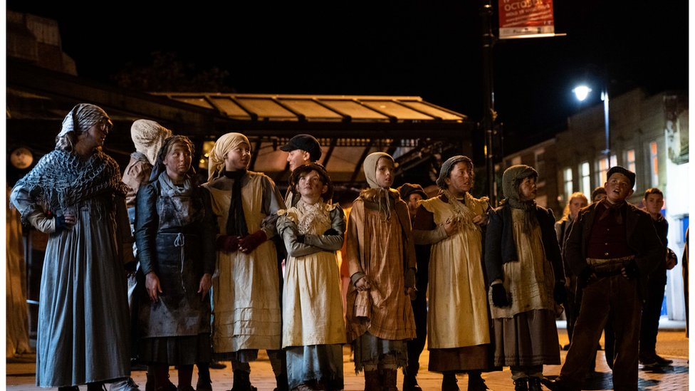 A scene from a Theatr Clwyd street production depicting the 1869 Mold Riots - a row of children in dirty 19th century-style clothes