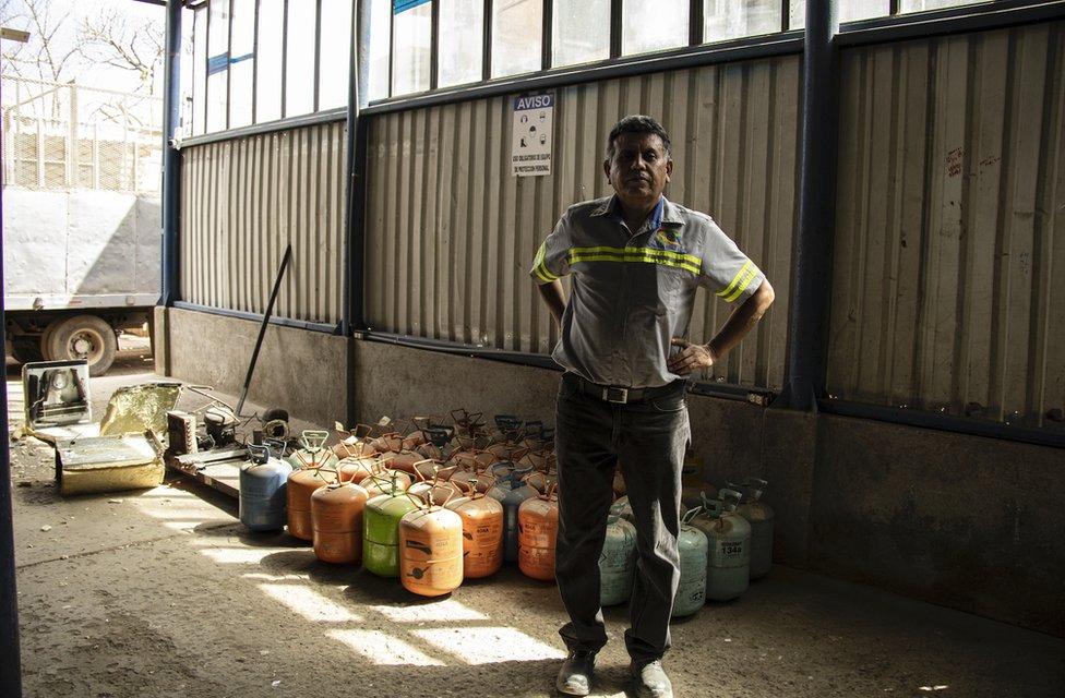 Ángel Toledo con bidones de gases refrigerantes en su empresa