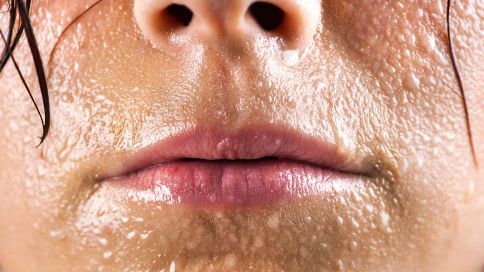 Rostro de una mujer cubierto en sudor