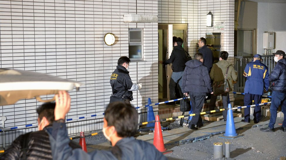 Police officers arrive for investigation of the apartment of abduction suspect Kabu Terauchi in Tokyo Monday, March 28, 2016