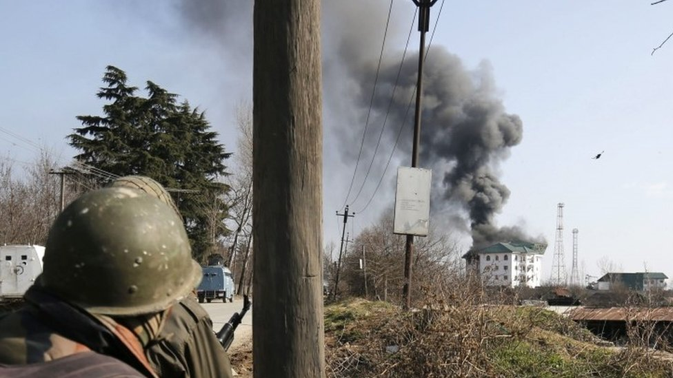 An Indian soldier looks on as columns of smoke come out from the top floor of building where militants are holed up during a gunfight near Srinagar (21 February 2016)