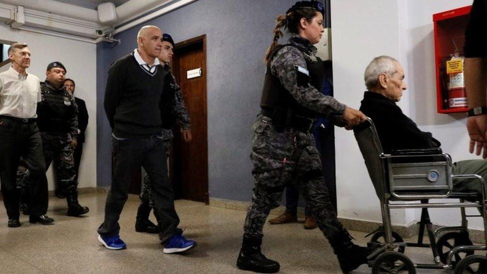 Nicola Corradi (en silla de ruedas) Armando Gómez (centro) y Horacio Corbacho (izquierda) abandonan la sala del tribunal en Mendoza, Argentina. Foto: 25 de noviembre de 2019
