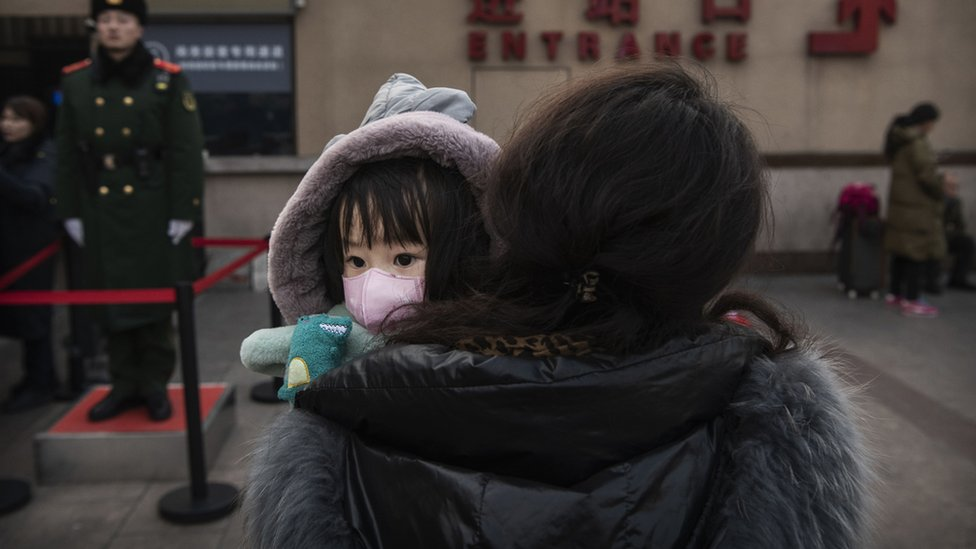 Niña en Pekín con una máscara protectora, en los brazos de una adulta.