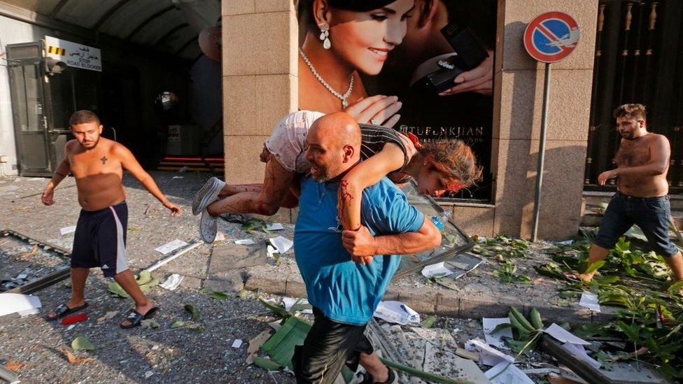 Un hombre porta a una joven herida por la explosión en Beirut.
