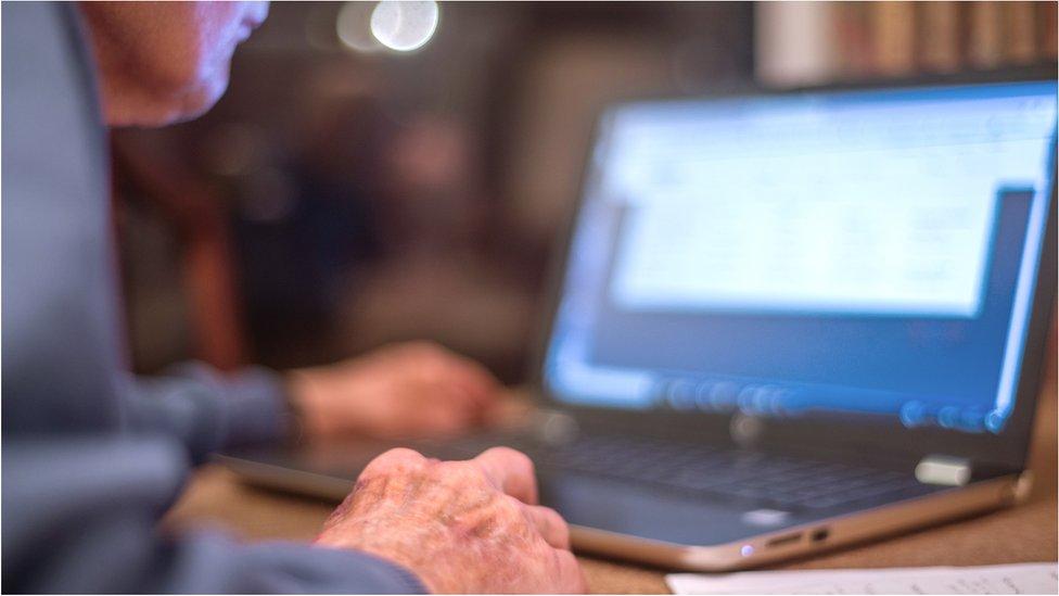 Older man checking computer