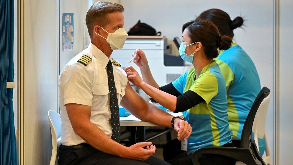 香港某社區疫苗接種中心內一位國泰航空公司外籍機長(左)接受一位女工作人員(右)注射科興新冠病毒疫苗(23/2/2021)