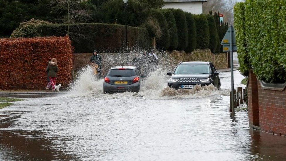 Cars drive through a flooded street in Great Barford, near Bedford,