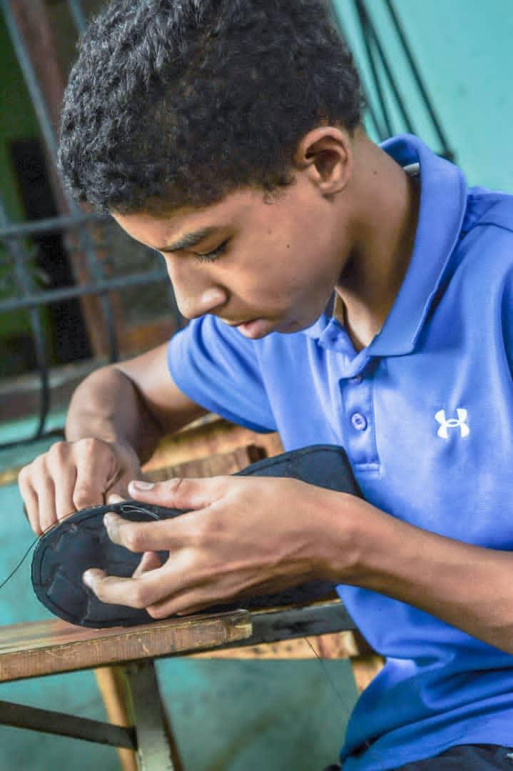 Andrés López trabajando las suelas de sus chanclas.