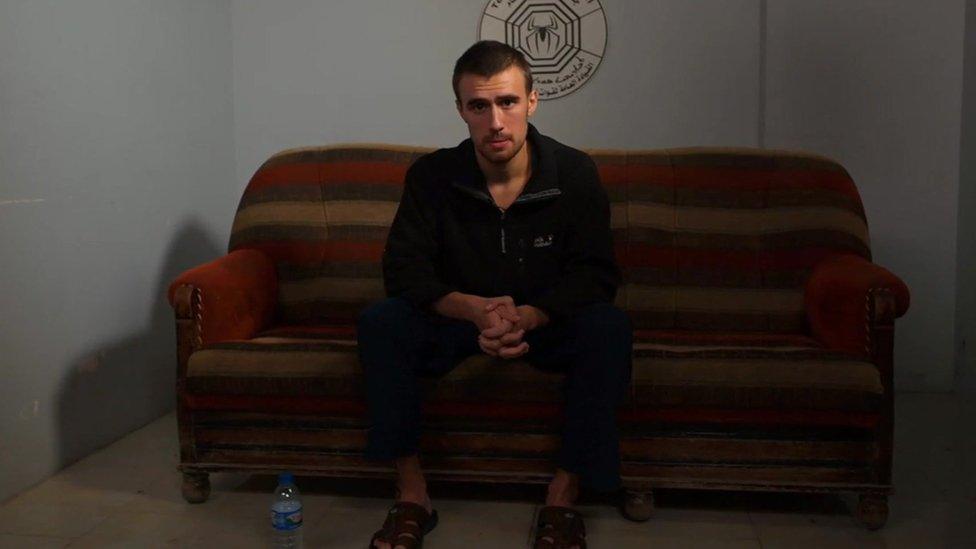 Jack Letts, aka Jihadi Jack, sitting on a striped sofa in a Kurdish jail in northern Syria