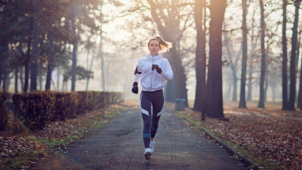 Joven mujer haciendo ejercicio por el bosque