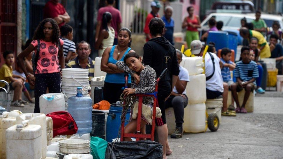 Personas en Venezuela haciendo fila para conseguir agua.