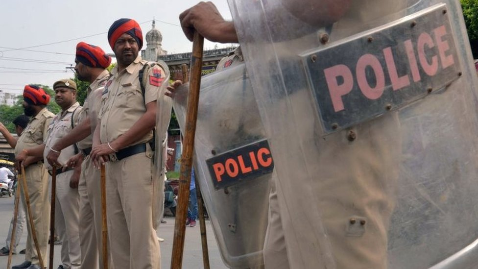 Indian police stand guard during a protest by Sikh demonstrators in Amritsar on October 19, 2015.