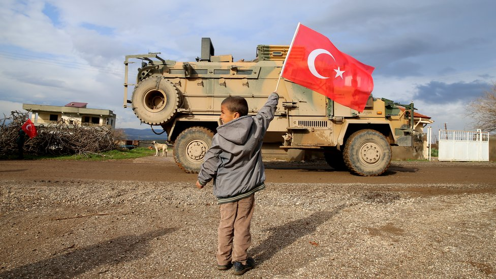 A photo taken from Turkey's Hatay province shows children greets soldiers with Turkish flags during Turkish military convoy consisting of approximately 300 armoured personnel carriers are on the way towards observation points in Syria's Idlib, on February 08, 2020 in Hatay, Turkey
