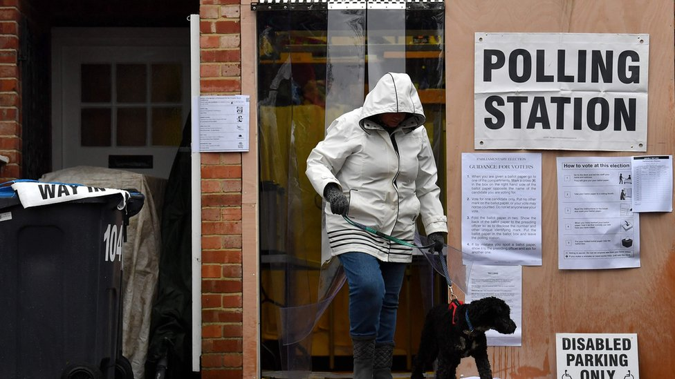 Voter leaves polling station in Croydon with her dog