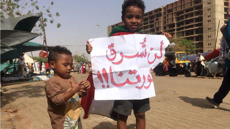 طفلان سودانيان يحملان لافتة ثورية